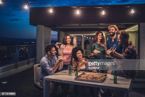 Jóvenes felices, tener una cena de fiesta durante la noche en una terraza.