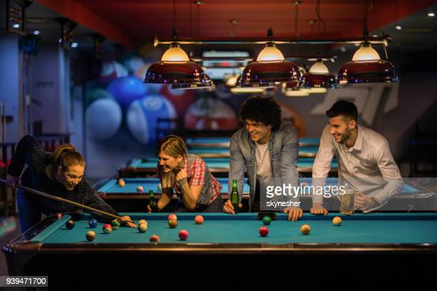 Young happy people having fun while playing billiard in a pub.