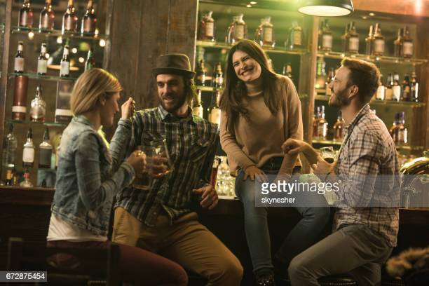 Young happy people having fun while spending the night out in a pub.