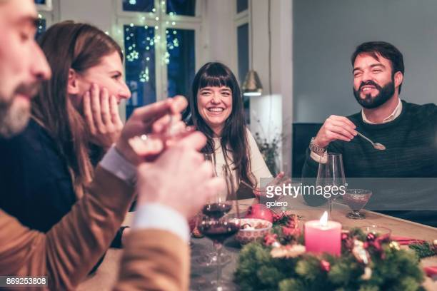 young happy people talking at christmas table