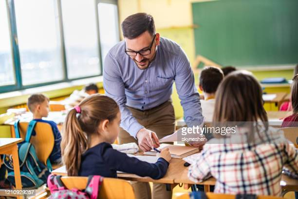 young happy professor assisting his elementary students on a class at school. - instructor stock pictures, royalty-free photos & images