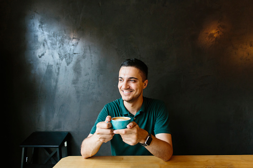 Young happy smiling man drinking coffee in a cafe - gettyimageskorea