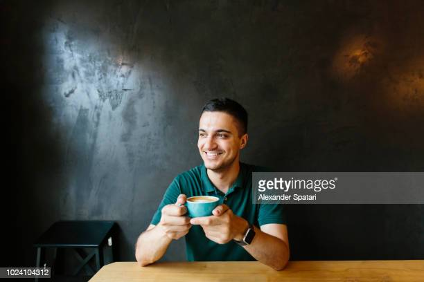 young happy smiling man drinking coffee in a cafe - coffee drink stock pictures, royalty-free photos & images