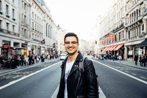 Young happy smiling man in glasses on the streets of London, UK - gettyimageskorea