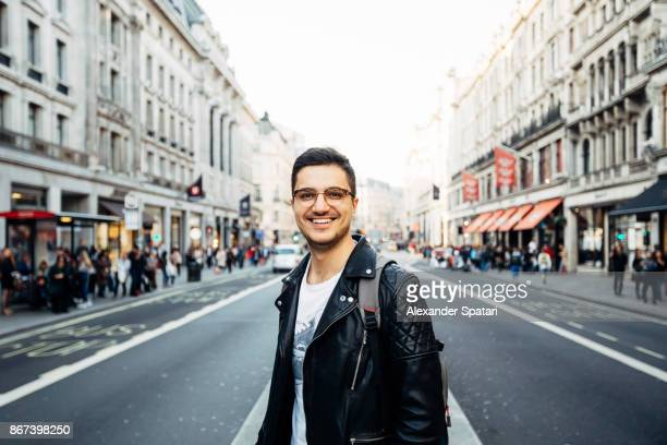 young happy smiling man in glasses on the streets of london, uk - jaqueta - fotografias e filmes do acervo