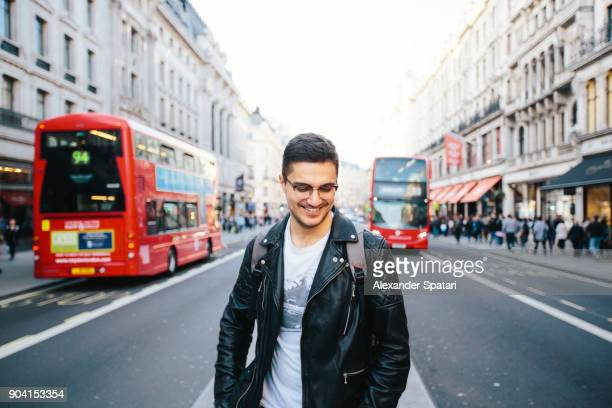 young happy smiling man in glasses on the streets of london, uk - double decker bus stock pictures, royalty-free photos & images