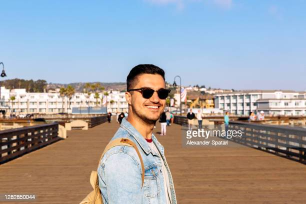 young happy smiling man in sunglasses on the pier - pismo beach stock pictures, royalty-free photos & images