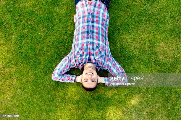 young happy smiling man laying in green grass - lying down foto e immagini stock