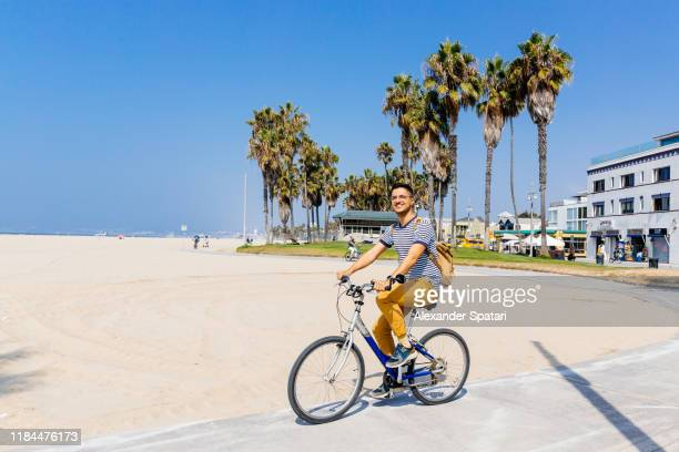 young happy smiling man riding a bike at venice beach, los angeles, california - la waterfront stock pictures, royalty-free photos & images