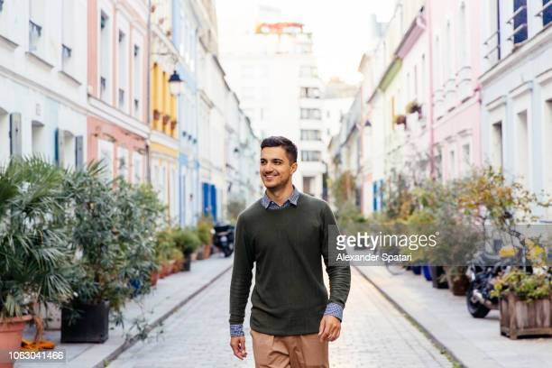 young happy smiling man walking on the street in paris, france - ein mann allein stock-fotos und bilder