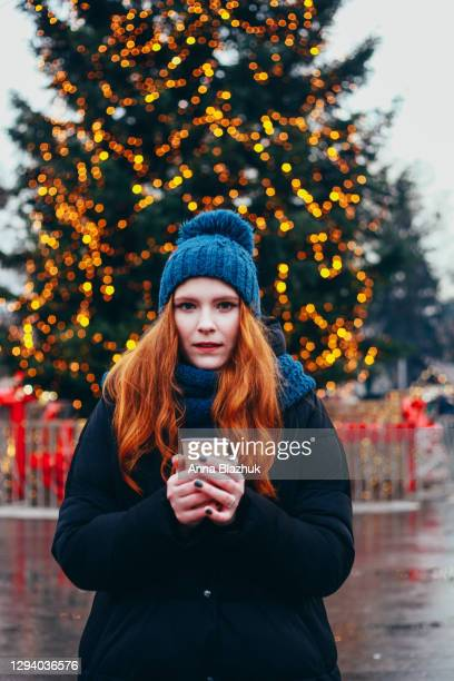 young happy smiling woman with red hair outdoors on street in warm winter clothes, christmas festive market decorated with fairy lights and pine tree. lifestyle for holidays. - dezember stock-fotos und bilder