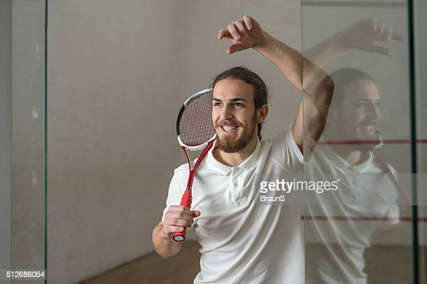 Young happy squash player with a racket.