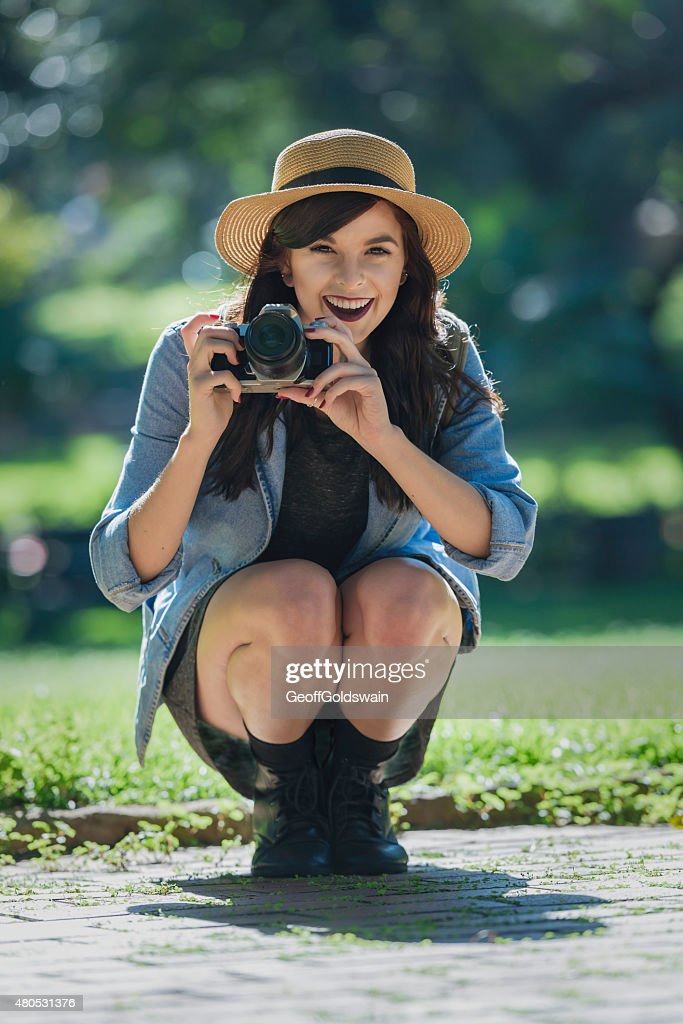 Young happy traveler exploring surrounds with film camera : Stock Photo
