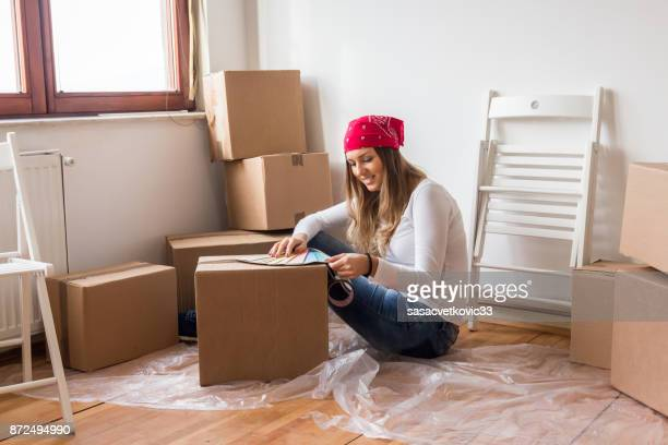 Young happy woman, a student, moved into a new apartment
