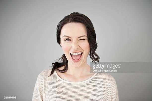 Young happy woman blinking eye, studio shot