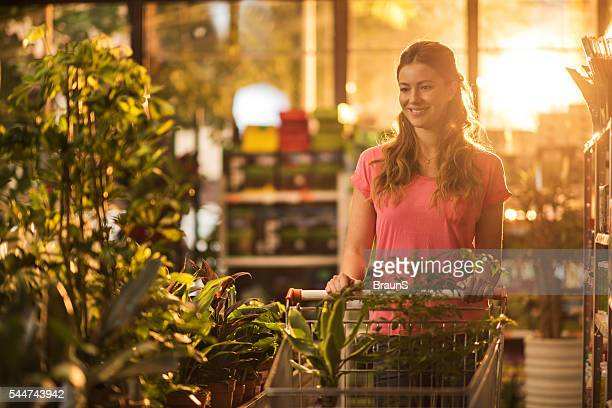 Young happy woman buying plants in a garden center.