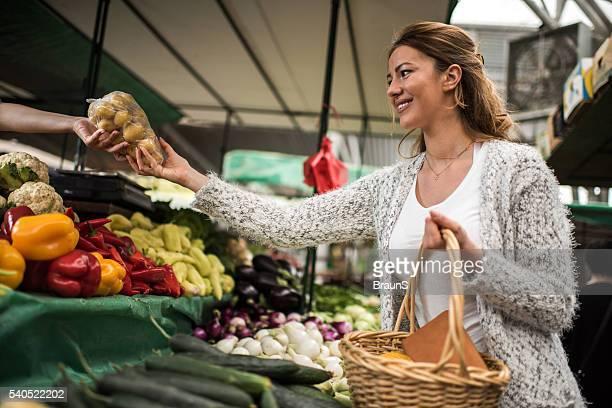 Junge glückliche Frau Kauf Kartoffel in die bauern market.