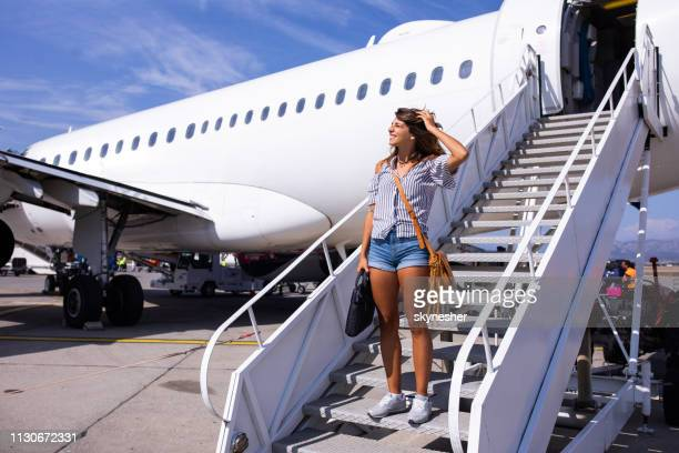 young happy woman disembarking the plane. - getting out stock pictures, royalty-free photos & images