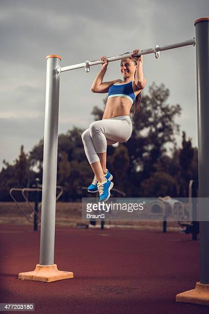 Young happy woman doing chin-ups on exercise equipment outdoors.
