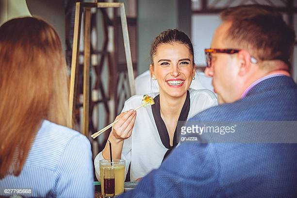 Young happy woman enjoying a lunch time at Asian restaurant.