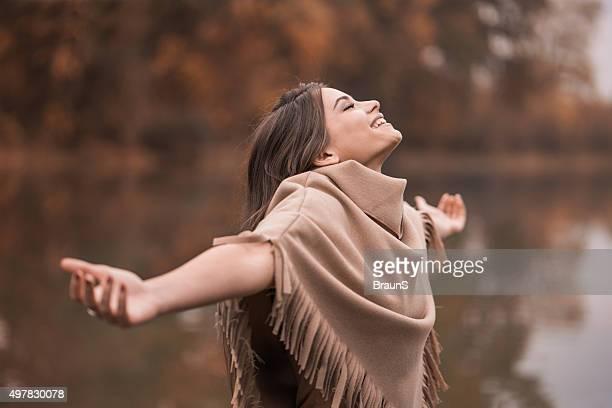 Junge glückliche Frau, die im Herbst Tag in der Nähe des Flusses.