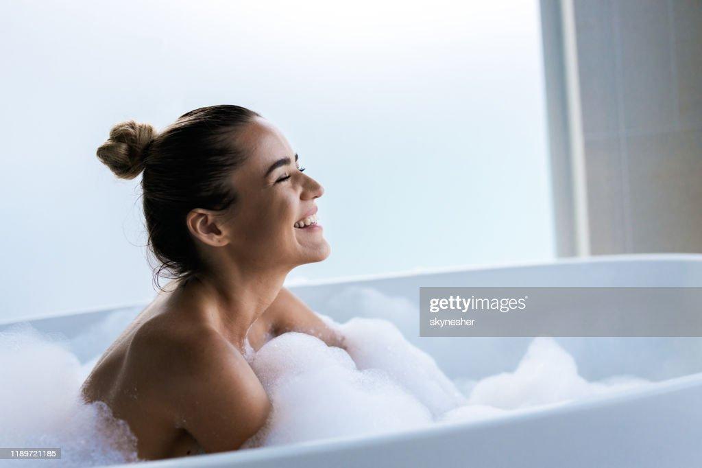 目を閉じて泡風呂で楽しんでいる若い幸せな女性。 : ストックフォト