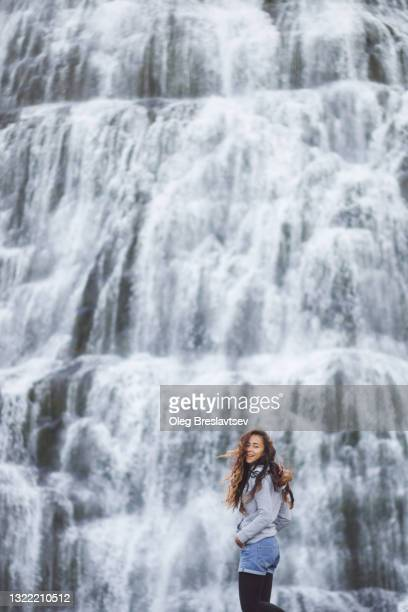 young happy woman enjoying view of dynjandi waterfall. breathtaking view of famous icelandic waterfall in westfjords - iceland stock pictures, royalty-free photos & images