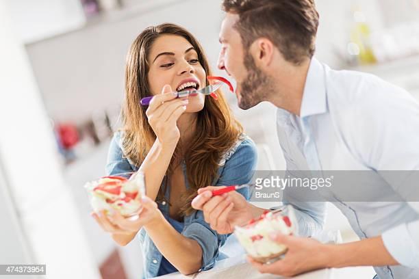 Young happy woman feeding her boyfriend with salad.