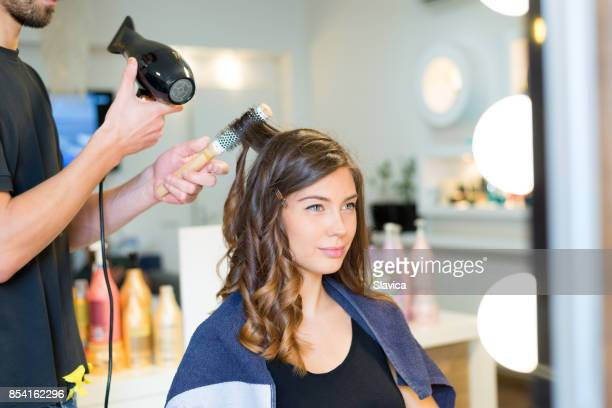 Young happy woman getting new hairstyle in modern hair salon