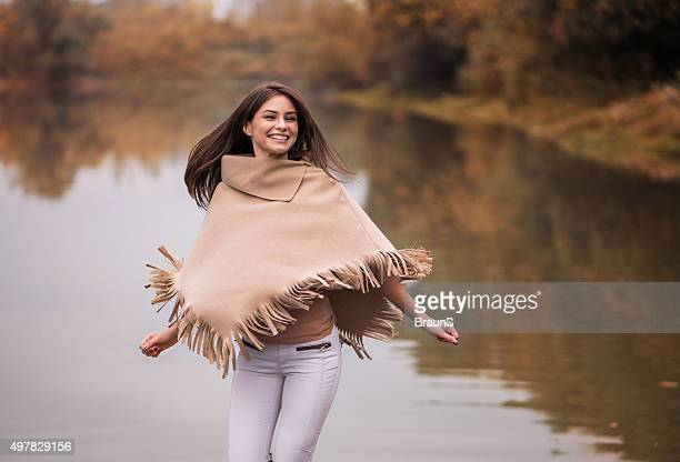 young happy woman having fun near the river. - poncho stock pictures, royalty-free photos & images