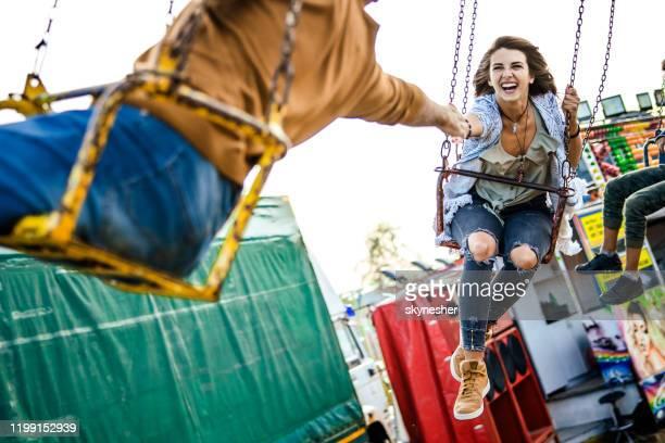 young happy woman having fun on a chain swing ride. - homem pegando mulher imagens e fotografias de stock