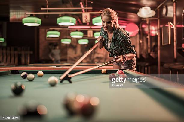 Young happy woman having fun while playing snooker.