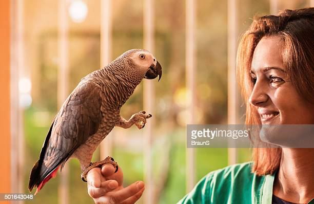 Young happy woman holding a gray parrot on her hand.