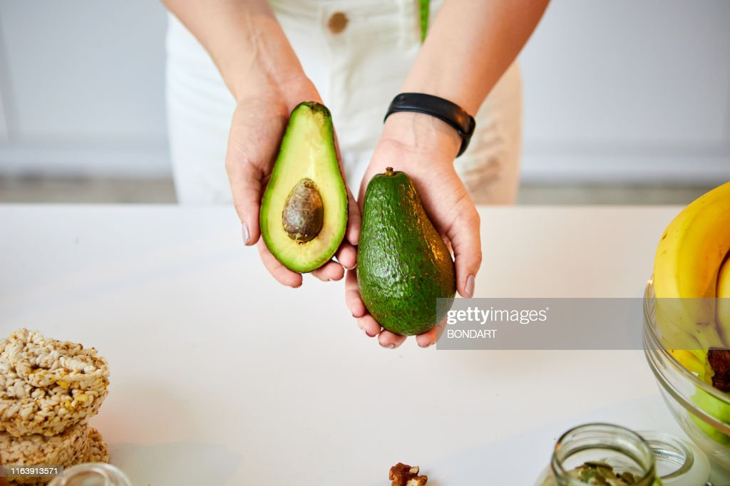 Young happy woman holding avocado for making salad in the beautiful kitchen with green fresh ingredients indoors. Healthy food and Dieting concept. Loosing Weight : Stock Photo