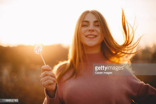 young happy woman holding lollipop while standing against sunset - golden hour stock pictures, royalty-free photos & images