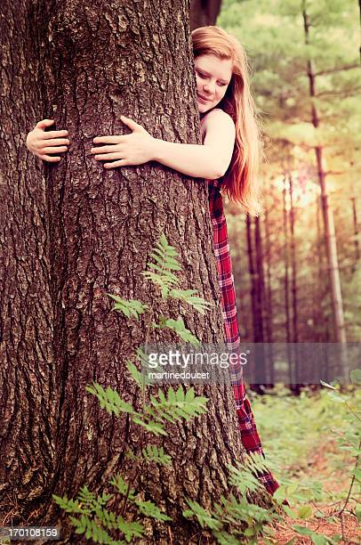 """young happy woman hugging a tree in the morning nature. - """"martine doucet"""" or martinedoucet stock pictures, royalty-free photos & images"""