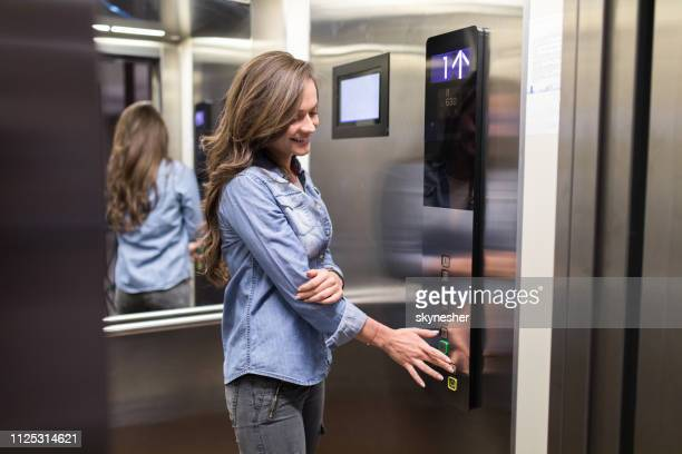 young happy woman inside of an elevator. - help:contents stock pictures, royalty-free photos & images