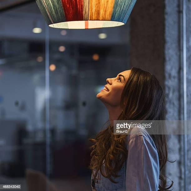 Young happy woman looking at lamp.