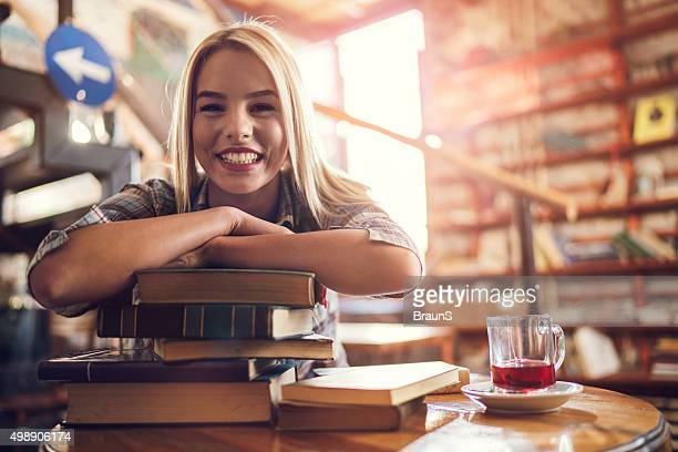 Young happy woman on a stack of books in library.