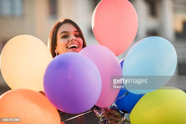 Young happy woman peeking behind group of colorful balloons.