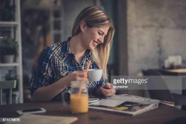 Gelukkig jongedame lezen van een tijdschrift in de winkel van de koffie.