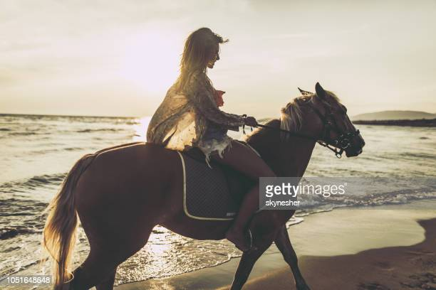 Young happy woman riding a horse on the beach.