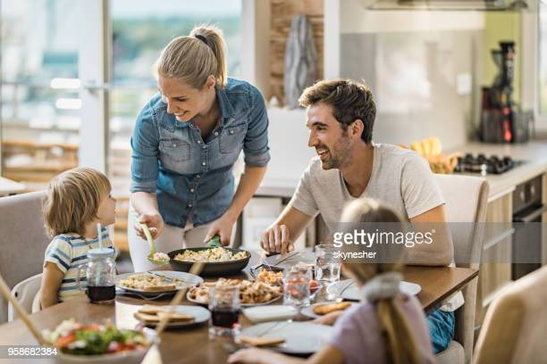 young happy woman serving lunch to her family at dining table. - evening meal stock pictures, royalty-free photos & images