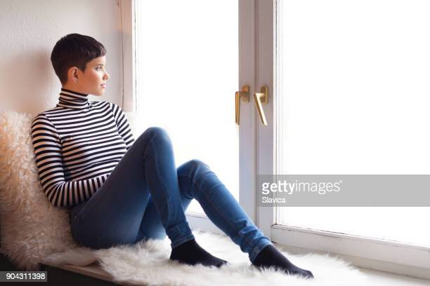 Young happy woman sitting in the window