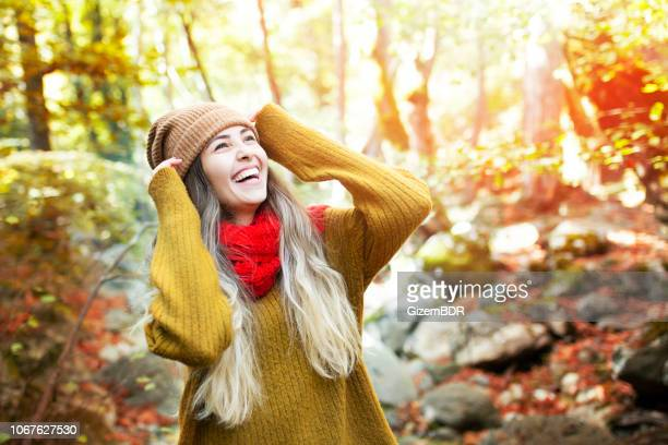 young happy woman smiles in the forest - winter coat stock pictures, royalty-free photos & images