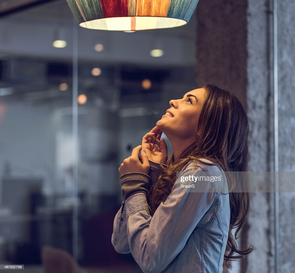Young happy woman standing and looking at lamp. : Stock Photo