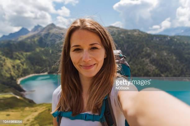 Gelukkig jongedame neemt een selfie op de top van de berg in de Zwitserse Alpen
