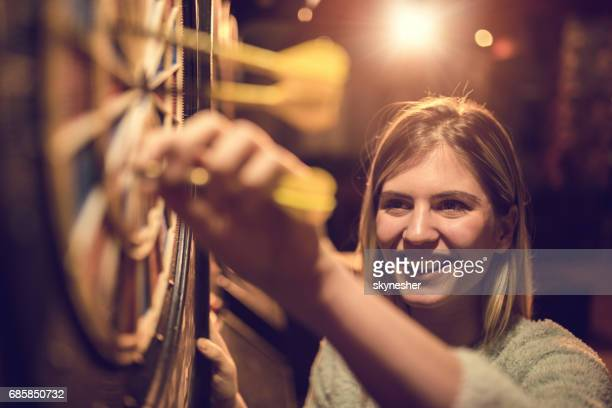 Young happy woman taking darts out of dart board.