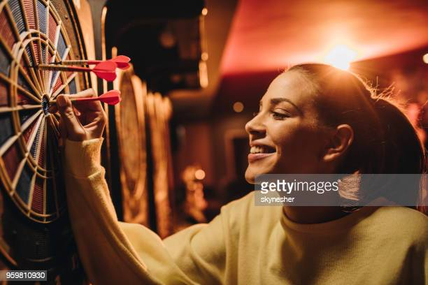 young happy woman taking darts out of dart board. - darts imagens e fotografias de stock