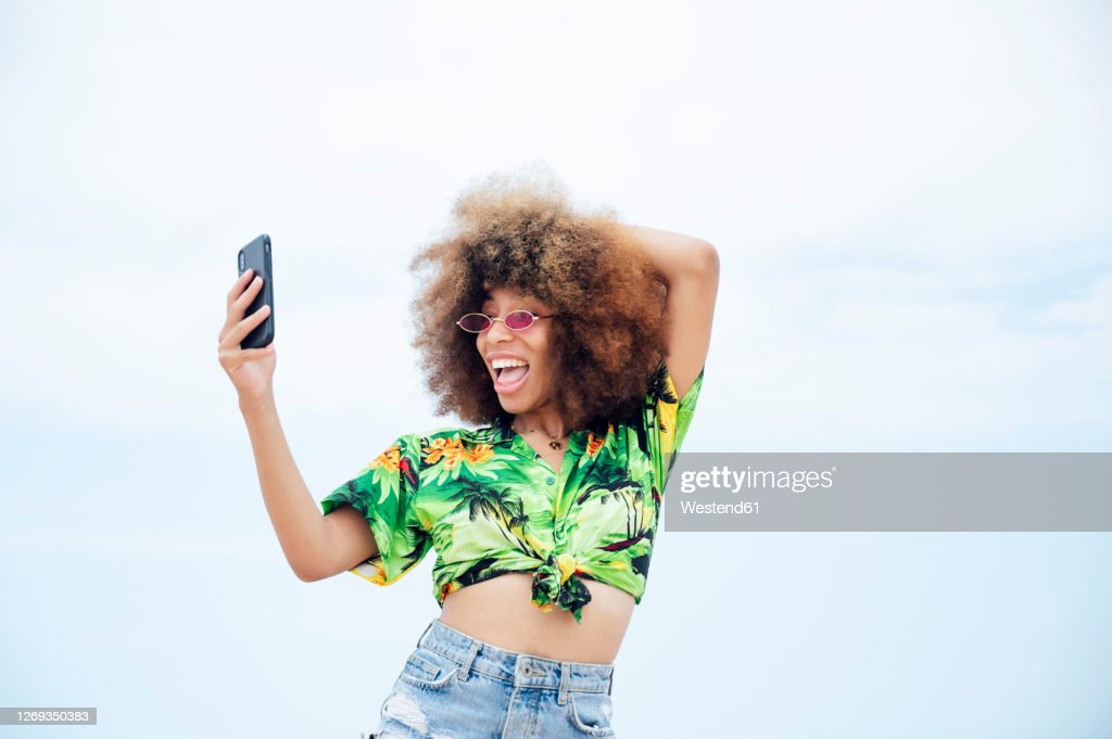 Young happy woman taking selfie at beach : Stock Photo